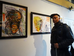 """Charles Curtis Blackwell stands in front of his work at Warehouse 416, where """"Invisible Black Men"""" is up through Feb. 28. – Photo: Wanda Sabir"""