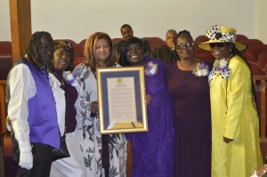 Carla Vaughn, center, presents a resolution from the Southeast Community Facility Commission to Mother Jackson's son McKinley Jackson and daughters Marilyn Jackson-Bay, Juanita Jackson-Banks and Peola Lane. – Photo: Patricia Winston