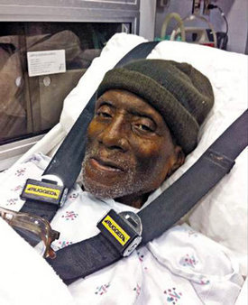 Herman Wallace manages a smile despite advanced liver cancer when he was wheeled out of prison on Oct. 1, 2013. A vengeful state re-indictment two days later became moot on Oct. 4, when he died – among loving family and friends. – Photo: Democracy Now