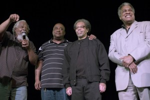 """Malik Rahim, who had regenerated support in the '90s for his Black Panther comrades, the Angola 3, and rescued Robert King when he was stranded by the Katrina flood, joyously announces the arrival at his own birthday party – planned to be celebrated once again without him – of Albert Woodfox. Beside Albert is his brother, Michael Mable, who picked him up at the prison, and, at right, Parnell Herbert, a childhood friend of Albert, who wrote the acclaimed stageplay, """"Angola 3."""" The party, held the evening of Albert's release, Feb. 19, was held at the Ashé Cultural Arts Center in New Orleans. – Photo: Max Becherer, AP"""