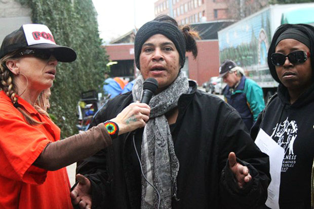 Trina, an unhoused San Francisco resident and WeSearcher, speaks at the press conference, flanked by Tiny of POOR Magazine and Queenandi XSheba, writer for POOR and teacher at Deecolonize Academy. – Photo: Laura Waxman