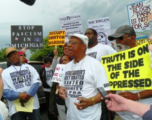 Rev. Edward Pinkney leads a rally against the Whirlpool-sponsored PGA tournament in Benton Harbor on May 26, 2012. That's Ralph Poynter, husband and advocate for then-imprisoned attorney Lynne Stewart on the left. – Photo: Voice of Detroit