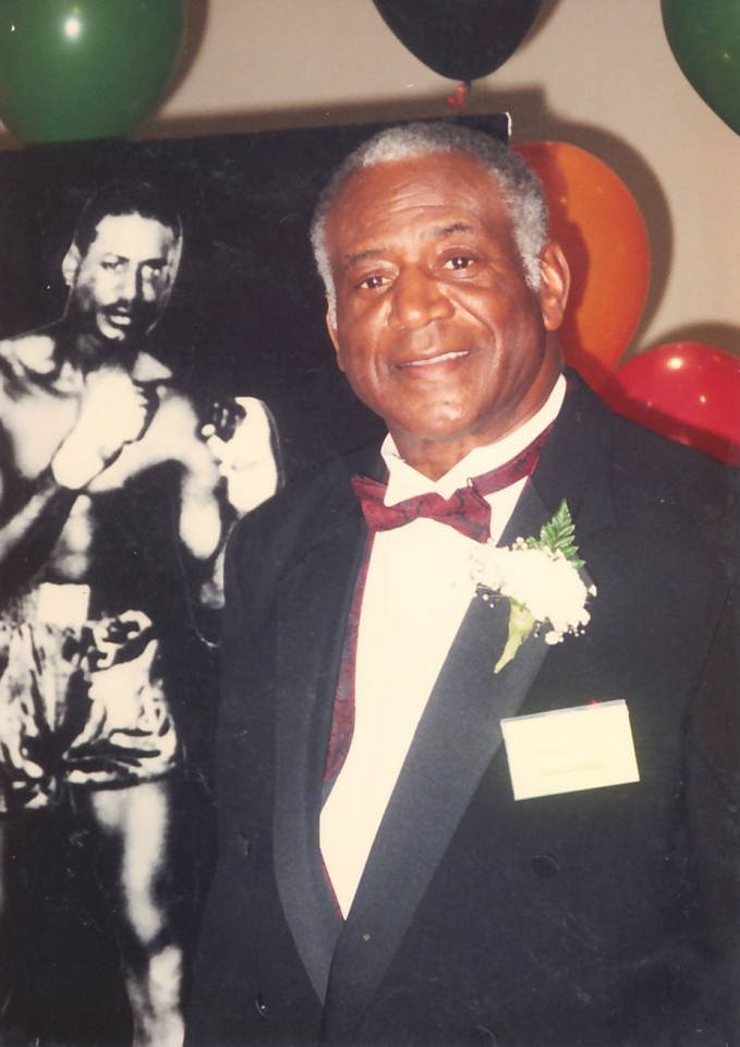 Handsome Sam Jordan stands next to a poster from his boxing career.