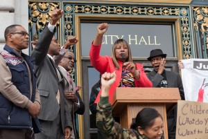 "Fists rise as Justice 4 Mario Woods Co-Chair Phelicia Jones shouts: ""All power to the people! Shame on San Francisco! Shame on the San Francisco Police Department! We are gathered here to bring unity, to fight as one, Black and Brown together, fighting for justice. … We are here to tell the powers that be in San Francisco, you will not get away with murder. … If we can't beat you in court, we'll beat you with our voting ballots!"" Archbishop Franzo King (right) stands behind her, cheering her on. – Photo: Pax Ahimsa Gethen"