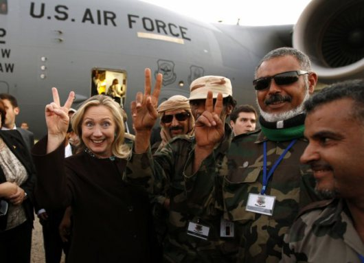 Hillary Clinton and Libyan soldiers claim victory after assassinating Muammar Qaddafi in October 2011. – Photo: Kevin Lamarque, Reuters