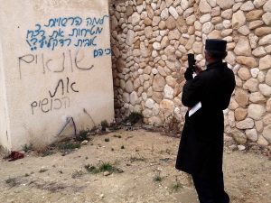 """African Hebrew Israelite spokesperson Immanuel Ben-Yehuda takes a photo of neighborhood graffiti. The top blue section of the graffiti, which was recently added to the wall, reads: """"Why are the authorities covering up the murder of Toveet Radcliffe? Because they…."""" The bottom black section of the graffiti, which was sprayed on the wall many years before, reads, """"… hate the n*****s."""" – Photo: David Sheen"""