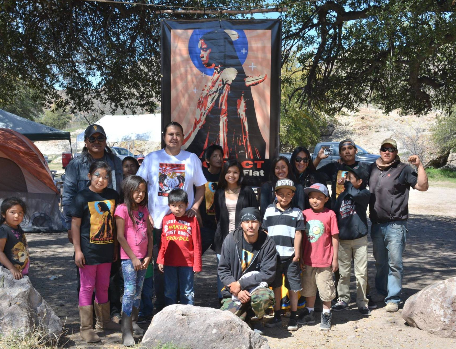 The San Carlos Apache Tribe camps at Oak Flat to protect the sacred site where Apaches have gone to pray for countless centuries and where coming of age ceremonies have traditionally been held. You can buy a Protect Oak Flat T-shirt with the beautiful artwork on the banner behind them by emailing apache.stronghold@gmail.com.