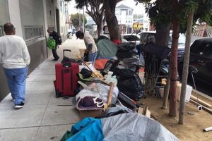 """On April 14, a week after Luis Gongora was murdered by police here in the """"tent city"""" where he lived, campers pack up after being told they had to move or all they own would be swept up and destroyed. Another friend of Luis, Carlos Guevara, came forward that day as the eighth witness to deny Gongora had lunged at police. He said that the city worker who told police Gongora had been swinging his knife had been going tent to tent demanding that everyone move, and Gorgora began stabbing a tree in anger and frustration. Less than 30 seconds after police arrived, he was dead. – Photo: Laura Waxmann, Mission Local"""