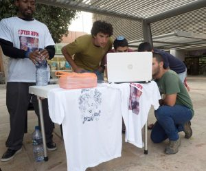Jewish seminary students watch a laptop playing an informational video about Toveet Radcliffe, also pictured on T-shirts being sold to raise funds to legally challenge the decision to close the Israeli army investigation into her death. – Photo: Dan Cohen