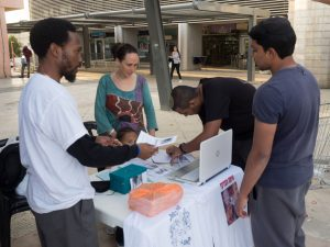 Shemohn and Khaya Osher (left) and other African Hebrews operate an informational table in front of Dimona City Hall to raise awareness about the life and death of community member Toveet Radcliffe. – Photo: Dan Cohen