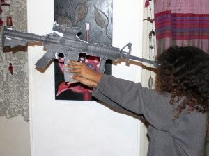 """Toveet's sister """"M"""" holds a model of Toveet's rifle to her head with one hand, as the IDF report posits Toveet did, and fails to reach the rifle's trigger with her other hand. – Photo: David Sheen"""
