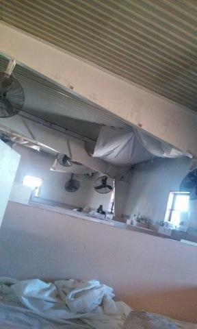"At Holman Prison, the problem of a leaking roof is ""solved"" by hanging tarps from the ceiling."