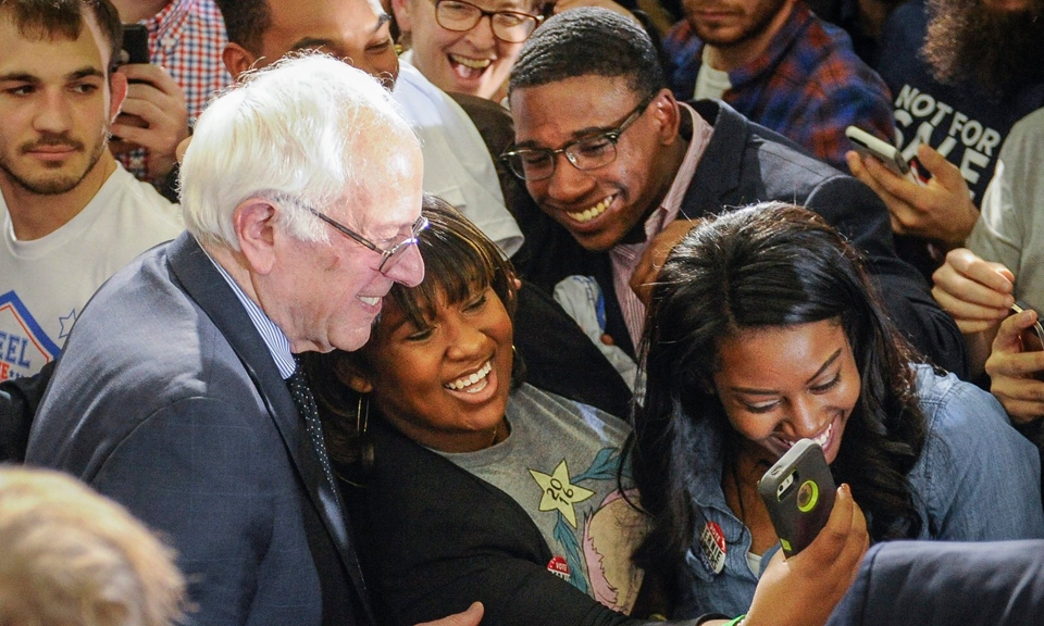 "Bernie is surrounded by supporters at Morehouse College earlier this year. Young Black voters are flocking to him, and older Blacks are recognizing that he is ""unbought and unbossed"" in the tradition of Shirley Chisholm. – Photo: John Amis, EPA"