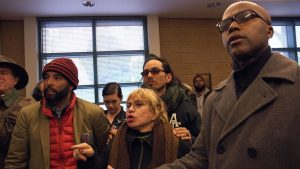 Frisco 5 hunger strikers Edwin Lindo (in watch cap), Cristina Gutierrez and Ilyich Sato (behind her), her son, a renowned rapper better known as Equipto, confront police at Mission Station on April 26. The hunger strike was Cristina's idea. – Photo: Peter Menchini