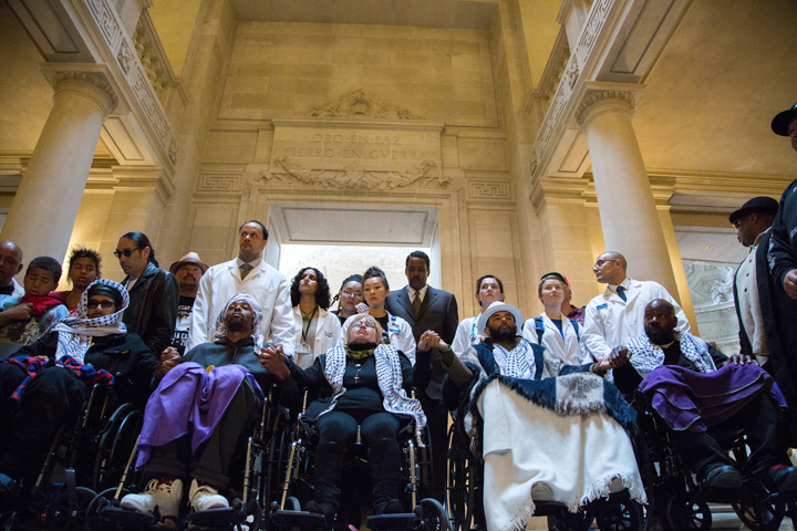 "The Frisco 5 hunger strikers (from left in wheelchairs) Ilych ""Equipto"" Sato, Sellassie Blackwell, Maria Cristina Gutierrez, age 66, Edwin Lindo and Ike Pinkston, clasping hands in solidarity, take a moment at City Hall before demanding to meet with Mayor Ed Lee in protest against police brutality. – Photo: Santiago Mejia, The Guardsman"