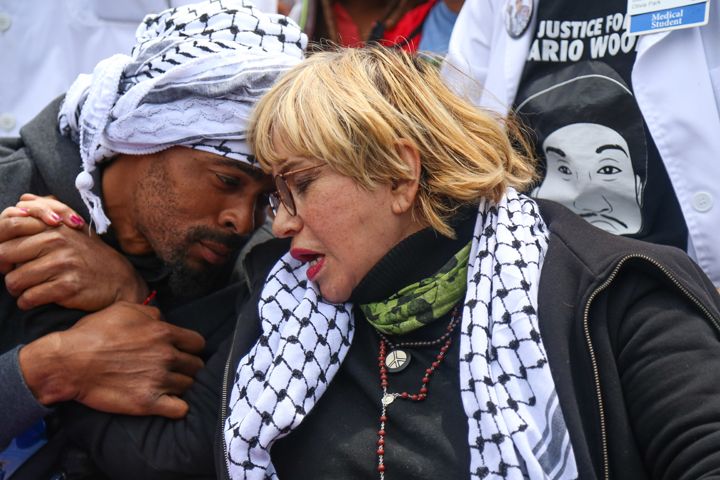 "Sellassie and Gutierrez embrace while being pushed in wheelchairs on Day 13 of their hunger strike during a rally against police brutality at City Hall, where they went to meet with Mayor Lee to demand the firing of Chief Suhr. Lee was a no show. Maria Cristina Gutierrez, 66, mother of rapper and fellow hunger striker Equipto and ""mama"" to all the Frisco 5, is the one who first proposed the hunger strike. – Photo: Natasha Dangond, special to The Guardsman"