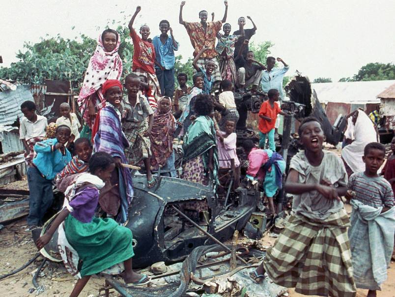 Somalian children dance on the wreckage of a U.S. Black Hawk helicopter brought down in a crash in October 1993 that killed 18 U.S. soldiers, whose bodies were dragged through the streets of Mogadishu. U.S. outrage over those deaths prompted President Bill Clinton to pull out of Somalia and not to risk the lives of U.S. troops to save the Black lives of Rwandans when the genocide began there the following year. – Photo: Dominique Mollard, AP-Stars and Stripes