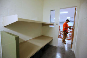 Since 2007, California has authorized $2.2 billion for the construction of county jail facilities throughout the state. The $270 million for more such construction that was added back just before the governor signed the budget would build and expand even more jails, at a time when jail populations are declining. Here, a construction worker puts the finishing touches on a new Madera County Jail cell in 2013. – Photo: Rich Pedroncelli, AP