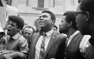 Muhammad Ali leaves the armed forces induction center with his entourage after refusing to be drafted into the armed forces in Houston, Texas, April 28, 1967. – Photo: AP