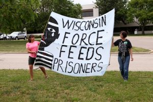 Wendy Turk, left, and Mary Jo Fesenmaier hold a banner decrying the force feeding of Wisconsin prisoners during a rally outside the state Department of Corrections headquarters in Madison on July 5. Hunger striking prisoners and their advocates are seeking an end to long-term solitary confinement. – Photo: Coburn Dukehart, Wisconsin Center for Investigative Journalism
