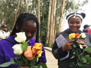 Girls who came from the Bayview Hunters Point YMCA to learn about the Buffalo Soldiers at the Presidio, the former army base where they were stationed in 1903-1904, enjoy the fragrance of the roses they laid on the soldiers' graves.