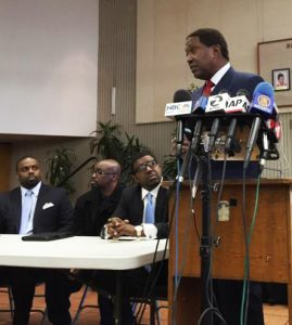 Attorneys from the powerful law firm of John Burris, from left, DeWitt Lacy, Lateef Grey and Adante Pointer, listen to Burris speak at a Dec. 11, 2015, press conference on the SFPD execution of Mario Woods. Burris' firm is among the most prominent and successful firms in the U.S. in holding police accountable. – Photo: KRON4