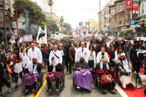 """In one of many dramatic events during their 17-day hunger strike, on May 3, the Frisco 5 – Ike Pinkston, Ilych """"Equipto"""" Sato, Selassie Blackwell, Cristina Gutierrez and Edwin Lindo – """"marched"""" in wheelchairs pushed by the doctors and medical students who tended to their health from the site of the strike, outside the Mission Police Station, to City Hall, where they expected to finally meet with the mayor. He stood them up, so they continued down the hall to the weekly Board of Supervisors meeting, then underway, and made passionate statements that probably speeded their success. They ended their strike after being hospitalized on May 7, and on May 19, SFPD Chief Suhr resigned, fulfilling their No. 1 demand. – Photo: Joel Angel Juárez, El Tecolote"""
