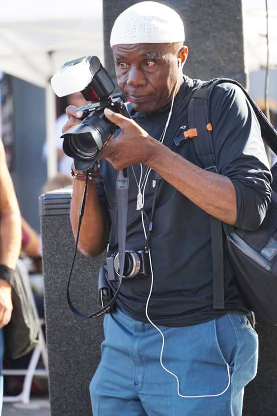 Kamau Amen Ra raises his camera to capture another masterpiece. – Photo: Wanda Sabir