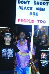 """Uncle Bobby joins the nightly protests in Ferguson on Aug. 24, 2014, with Jasiri X and David Banner. Their sign's message, """"Black men are people too,"""" suggests the phrase """"Black Lives Matter,"""" which hadn't yet caught on but soon became the rallying cry for the movement to end police terror."""