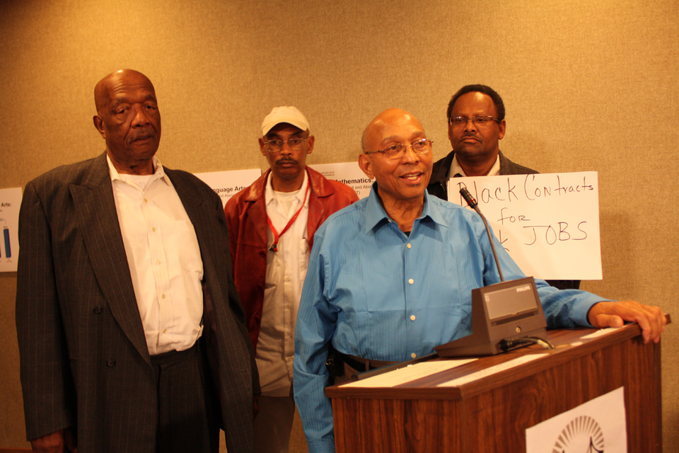 """Dr. Willie Ratcliff, Bay View publisher and owner of Liberty Builders, campaigning for a greater role for Blacks in school construction, testified at a School Board meeting, backed by fellow contractors Charlie Walker and Muhammad al-Kareem and by Mike Brown, whose sign tells a fundamental truth, """"Black contracts for Black jobs!"""" – Photo: Ken Johnson"""