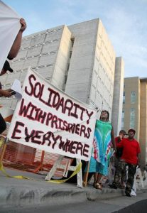 Cynthia Fox of the Inside-Outside Alliance in Durham, N.C., stands beside a banner outside the Durham County Jail entrance on Aug. 9, 2016, to protest mass incarceration and call attention to the National Prison Strike Sept. 9 against uncompensated and low-wage prison labor. – Photo: Mark Schultz