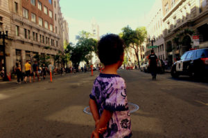 Lil Black boy in street watches cop downtown Oakland