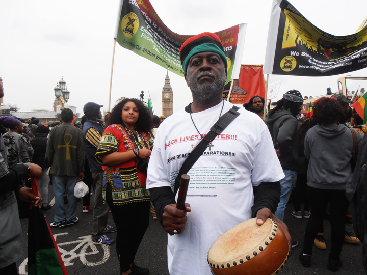 """Baba Jahahara Amen-RA Alkebulan-Ma'at stands with thousands of other reparationists on Emancipation Day, 1 Mosiah (August) 2016, for three minutes of silence for the Ancestors on the Westminster Bridge in London, England. Behind them is the British Parliament – House of Commons and House of Lords – with the """"Big Ben"""" clock tower, where a major rally was later held. Petitions demanding reparations were also delivered to No. 10 Downing Street, the official residence of the British prime minister."""