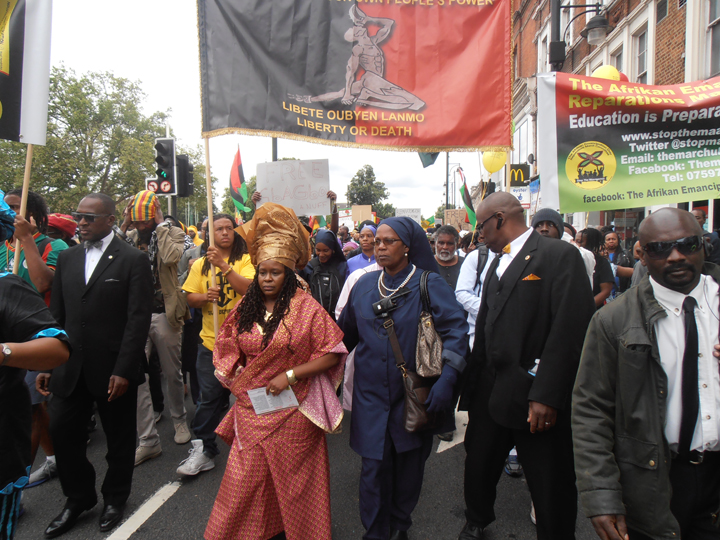 """Leader Esther Stanford Xosei leads the march from Brixton to Parliament. The Afrikan-Haitian banner says """"Reparations by Our Own People's Power! Liberty or Death!"""""""
