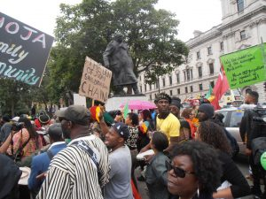 Reparationists march past the statue of the criminal and former Prime Minister Winston Churchill, at Parliament Square.