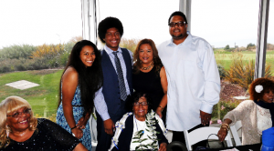 Mary Wilson's grandson Breland Tillmon and his family presented his grandmother with two leis made of 100 one dollar bills to welcome her to a new stage of life. At left is Grandma Mary's daughter Lillian, at far right her daughter Marilyn and behind her are Jazarae, Breland, Mary and Byron.