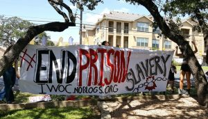 Activists hold a banner while protesting at Texas Correctional Industries' showroom in south Austin, Texas, in solidarity with the National Prison Strike on Sept. 9, 2016. – Photo: Kit O'Connell