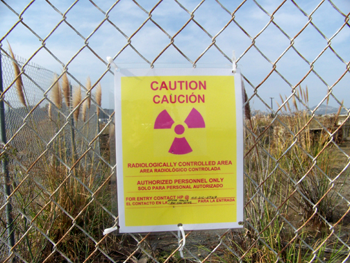 """When this photo was taken in 2007, these """"Caution"""" signs were everywhere, warning people that the area is radioactive. Yet construction of new homes that families are already living in went on unabated. – Photo: Bob Nichols"""