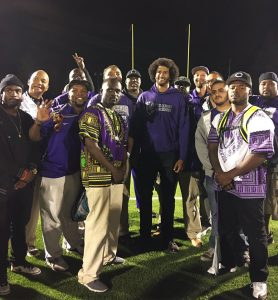"""On Sept. 23, Colin Kaepernick attended the Castlemont High football game in East Oakland, telling the team, """"You stood for me. So I had to come out and stand with y'all."""" During the national anthem, the team lay on their backs with their hands in the air while Kaepernick kneeled beside them. On the sideline for this photo, Kaepernick wore a Castlemont hoodie; in the locker room, he wore a Muhammad Ali shirt. – Photo: @ CastlemontFB"""
