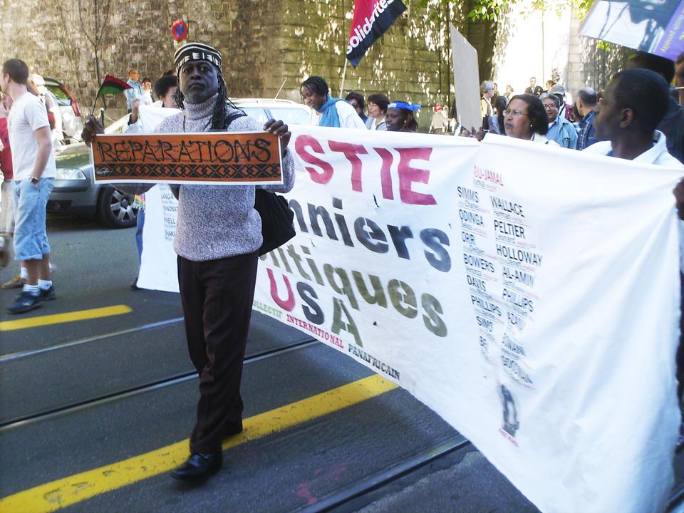 Jahahara-carries-'Reparations'-by-Emory-Douglas-at-UN-Durban-Review-Conf-Geneva-0409-by-Kali-Akuno-web, Un-ban the Bay View!, Behind Enemy Lines
