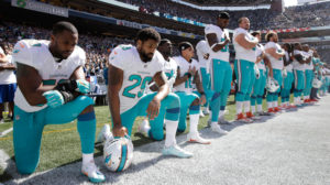Showing solidarity with Colin Kaepernick, four Miami Dolphins – Jelani Jenkins, Arian Foster, Michael Thomas, and Kenny Stills – kneel during the national anthem at their game Sunday against the Seahawks, who reneged on their plan for the whole team to protest. – Photo: Stephen Brashear, AP