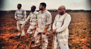 Prisoners – slave laborers – pause for a moment from their back-breaking work in a hot Texas field.