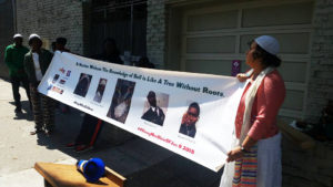 At right, holding the banner honoring all four young men, is Yolanda Banks Reed, community leader with the Hebrew Cultural Community. – Photo: Poor News Network