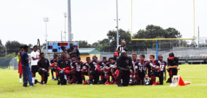 """Members of the Texas youth football team, the Beaumont Bulls, take a knee to """"protest violence against Black youth"""" during the national anthem before their Sept. 10 game. – Photo: April Parkerson"""