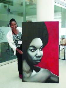 Wanda Sabir and Nina Simone at Dillard University: Dwayne Conrad, the artist who designed the Black Arts Movement conference brochure cover, had a large portrait of Nina Simone on display. I couldn't resist posing with the revolutionary sister in the Dillard University lobby where vendors sold books, jewelry, paintings and recordings. – Photo: Wanda Sabir