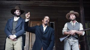 Nat Turner (Nate Parker) preaches the gospel while his owner (left) and patron (right) listen.