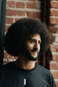 "Pleased with a job well done, Kaepernick smiles at the end of a long day. He muses: ""A lot of these communities have been oppressed for so long and talked down to for so long that it might take one person to spark that thought or that confidence that, 'You know what, my life matters, what I do matters, and I can succeed regardless of the oppressive nature of the system I have been put in.'"" – Photo: Katrina Britney Davis, The Undefeated"