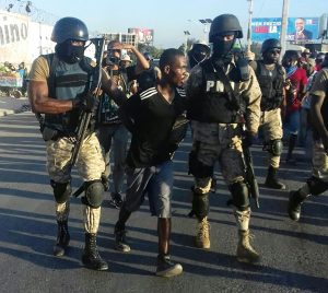 Haiti-election-protest-masked-police-arrest-protester-1216-by-HIP-web-300x268, Resisting the lynching of Haitian liberty!, World News & Views