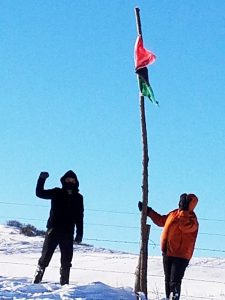 POOR-in-Standing-Rock-Tibu-Aselah-w-RBG-flag-122916-by-PNN-225x300, We are all connected, from Standing Rock to Oakland, National News & Views