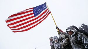 Standing-Rock-vets-march-hold-flag-against-strong-winds-120516-by-AAP-300x169, Veterans at Standing Rock offer long overdue apology to Native elders, National News & Views